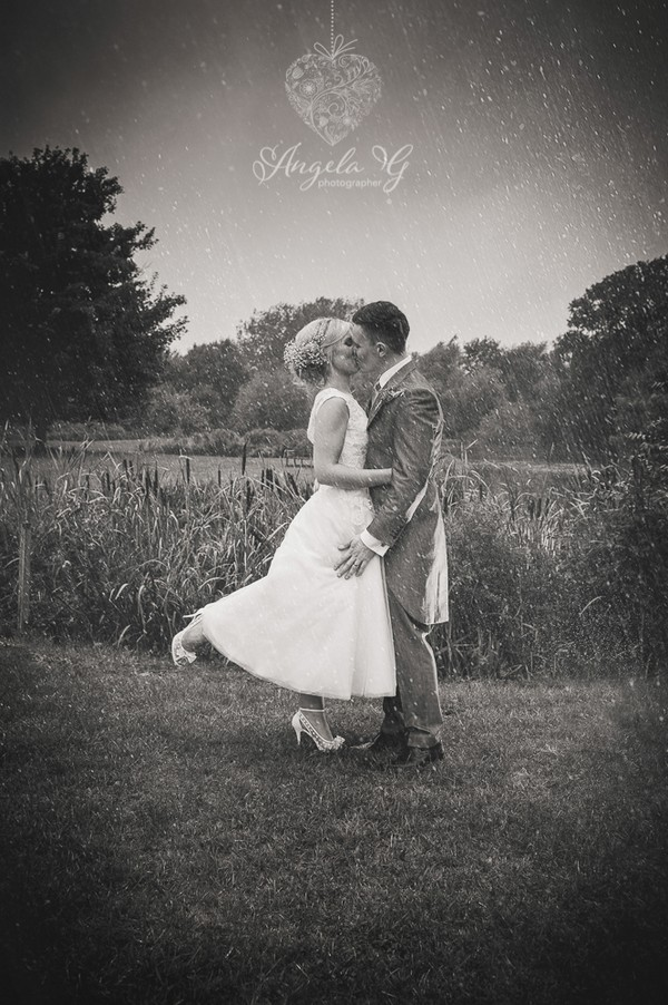 Bride and groom kissing in rain - Picture by Angela G Photographer