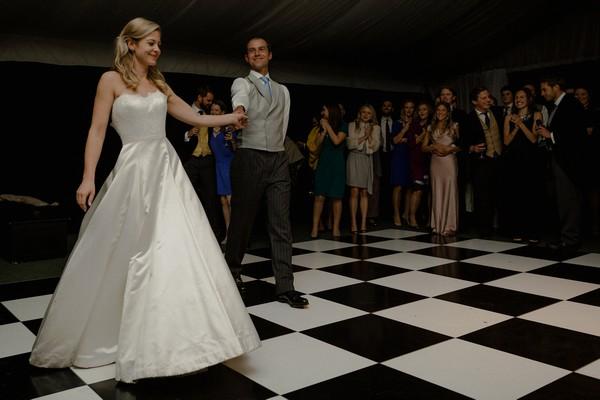 Bride and groom walking onto dance floor for first dance