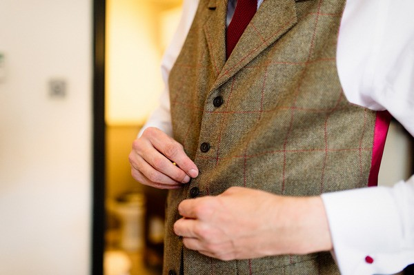 Groom Doing Up Buttons on Tweed Red Check Waistcoat
