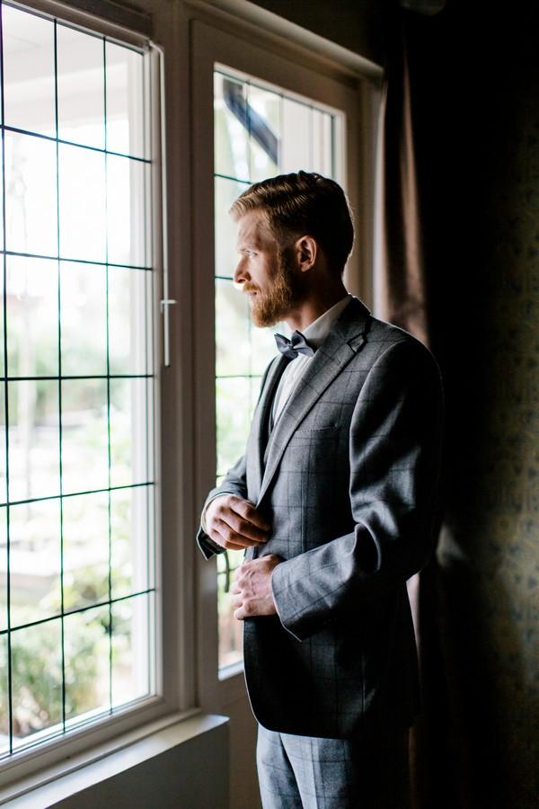 Groom fastening jacket as he looks out of window