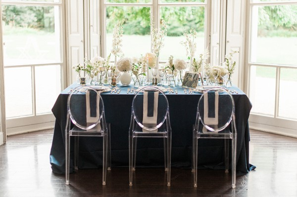 Wedding table with navy blue tablecloth and ghost chairs