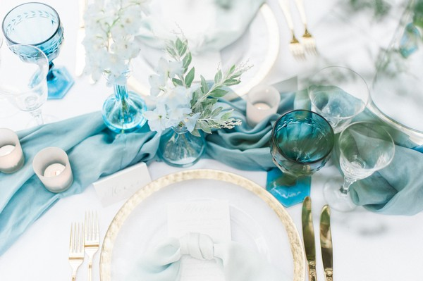 Blue silk runner and blue glassware on wedding table