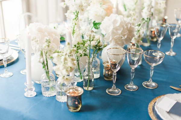 Bottles and vases of white flowers on wedding table