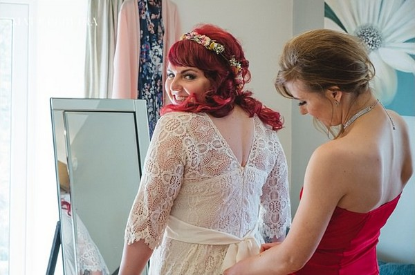 Bride looking over shoulder as dress is done up