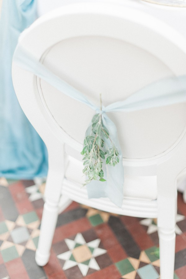 Light blue ribbon and foliage tied to back of wedding chair