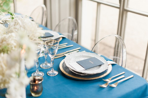 Place setting on wedding table with navy blue tablecloth
