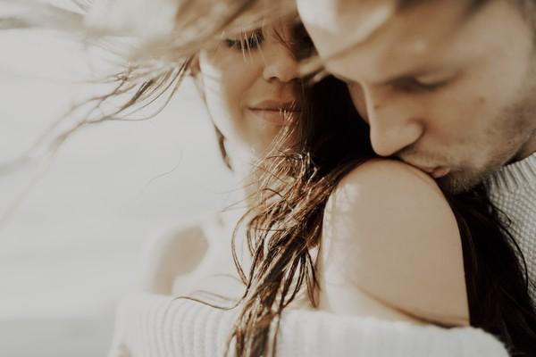 Man kissing fiancée's shoulder