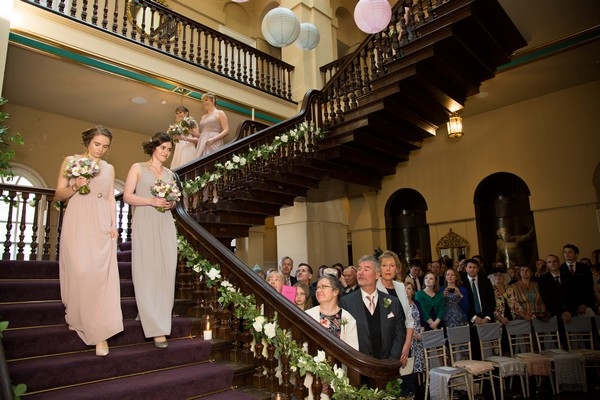 Bridesmaids walking down stairs at Kings Weston House