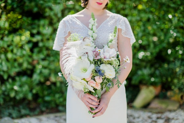 Bride holding bouquet with ostrich feathers