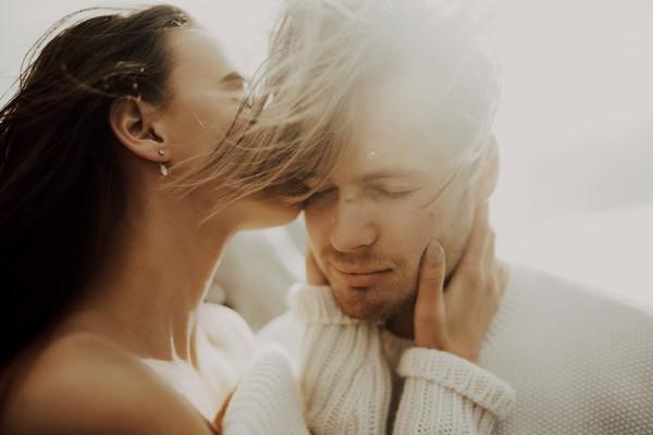 Woman kissing fiancé on cheek