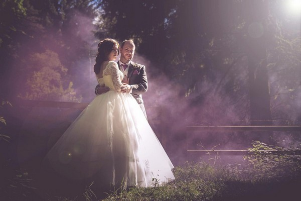 Bride and groom standing in light mist and hazy sunshine - Picture by Simon Emmett Photography