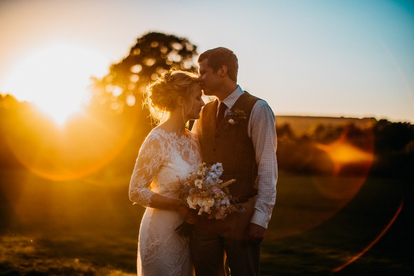 Groom kissing bride on head in hazy sunshine - Picture by Tom Smith Photography