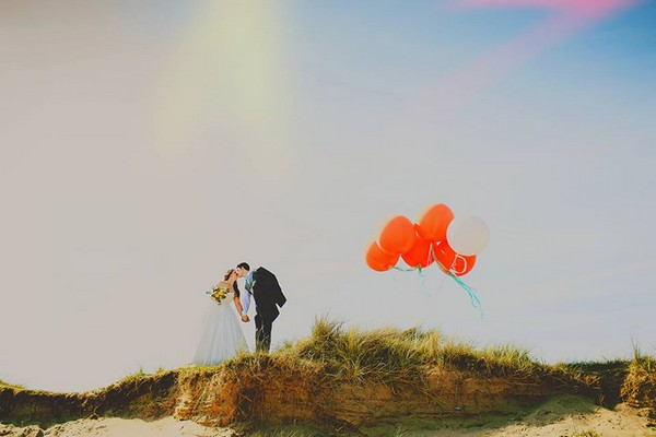 Bride and groom kissing on top of a hill next to orange balloons - Picture by Silver Birch Photography