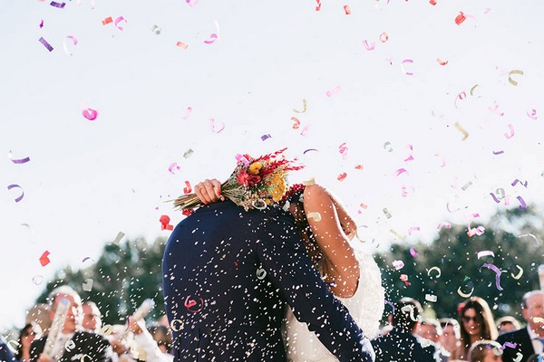 Bride and groom hugging as confetti falls around them - Picture by Sara Lobla