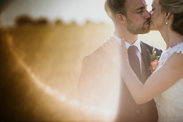 Bride and groom kissing a sun catches camera lens - Picture by Lee Dann Photography