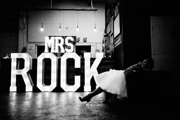 Bride sitting near 'Mrs Rock' illuminated letters - Picture by Vickerstaff Photography