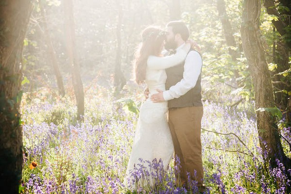 Bride and groom standing amongst flowers in hazy sunshine - Picture by Andrea Kuehnis Photography