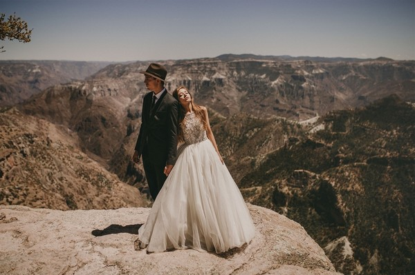 Bride and groom standing on cliff enge - Picture by Pablo Laguia
