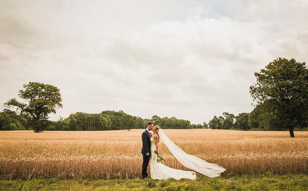 Bride and groom kissing in front of field of wheat - Picture by James Andrew Photography