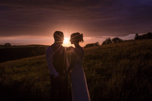 Bride and groom holding hands at sunset with the sun shining between their heads - Picture by Chris Kemp Photography
