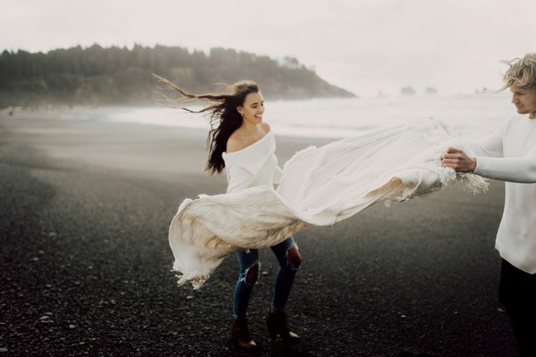 Couple with blanket blowing in wind on La Push beach