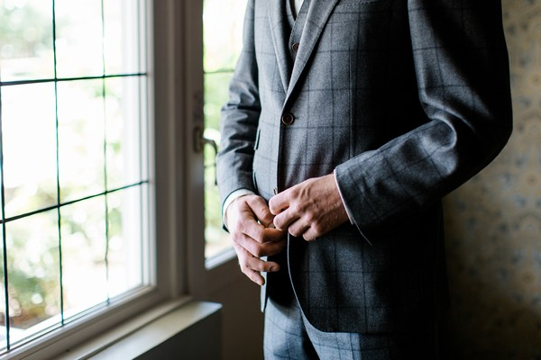 Groom fastening buttons on his jacket