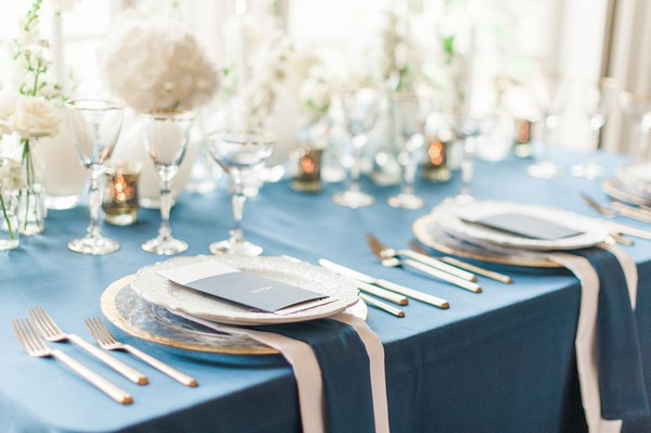 Place settings on navy blue styled wedding table