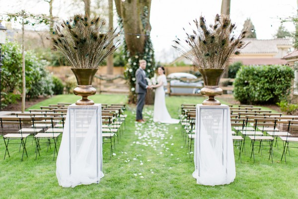 Large urns of peacock feathers at entrance to wedding ceremony