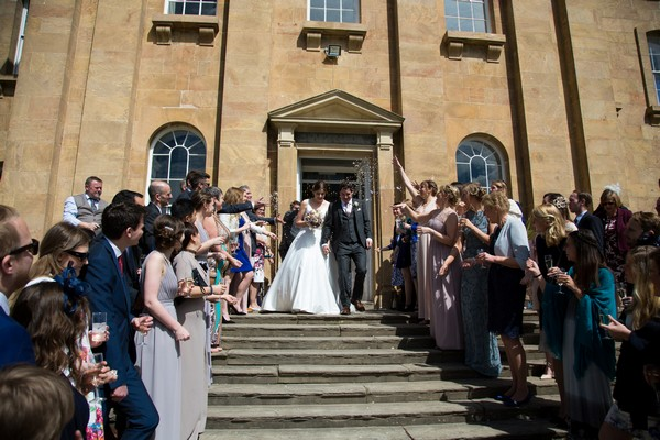 Bride and groom walking down steps outside Kings Weston House