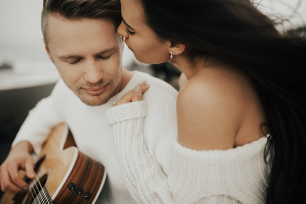 Man playing guitar to fiancée