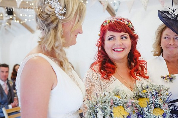 Brides smiling at each other at altar