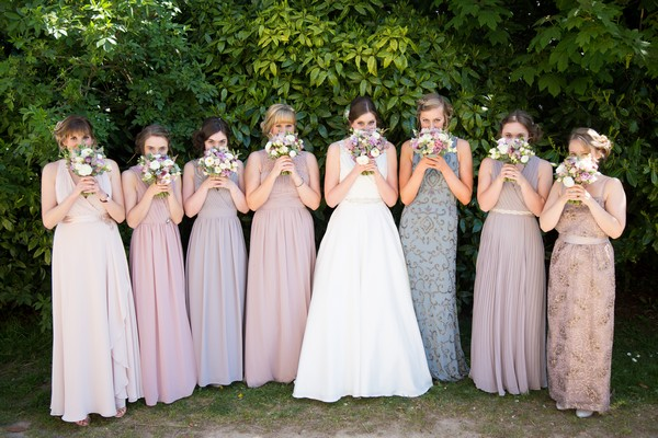 Bridesmaids with bouquets in front of their faces