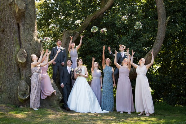 Bridesmaids throwing bouquets in the air