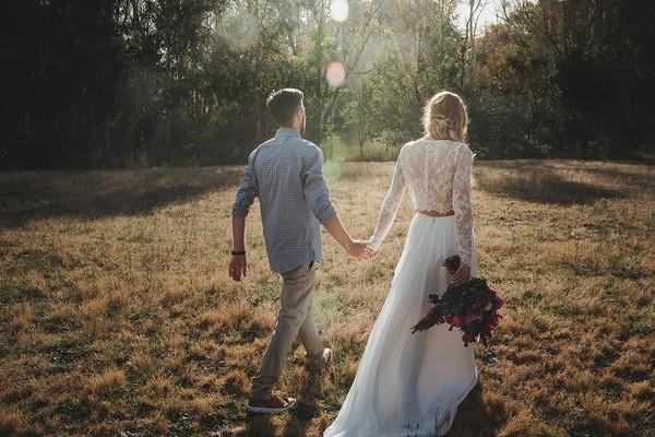 Bride and groom walking across field holding hands