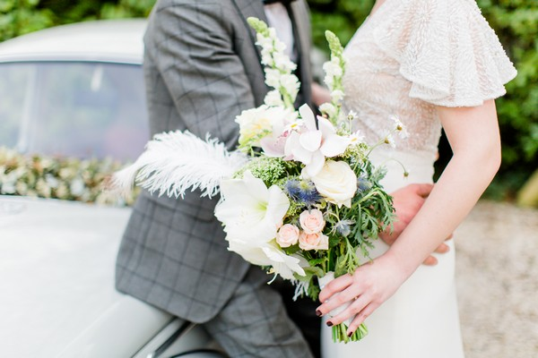 Groom with arms around bride's waist as she holds bouquet