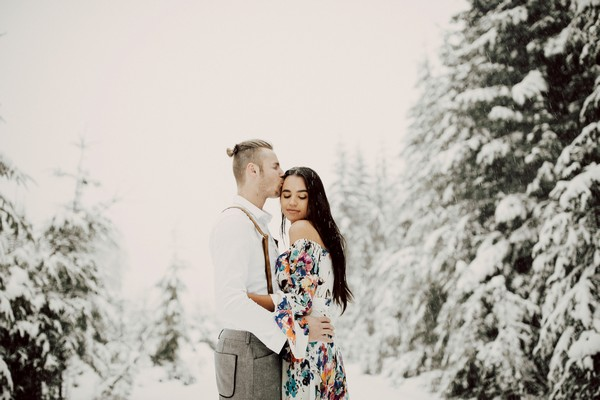 Man kissing fiancée's head in snow