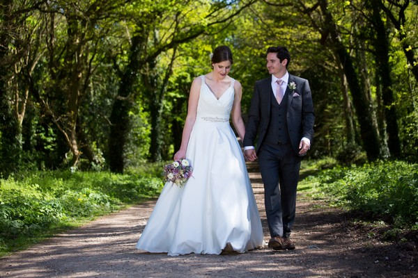 Bride and groom walking holding hands in grounds of Kings Weston House