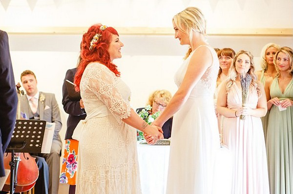 Brides holding hands facing each other