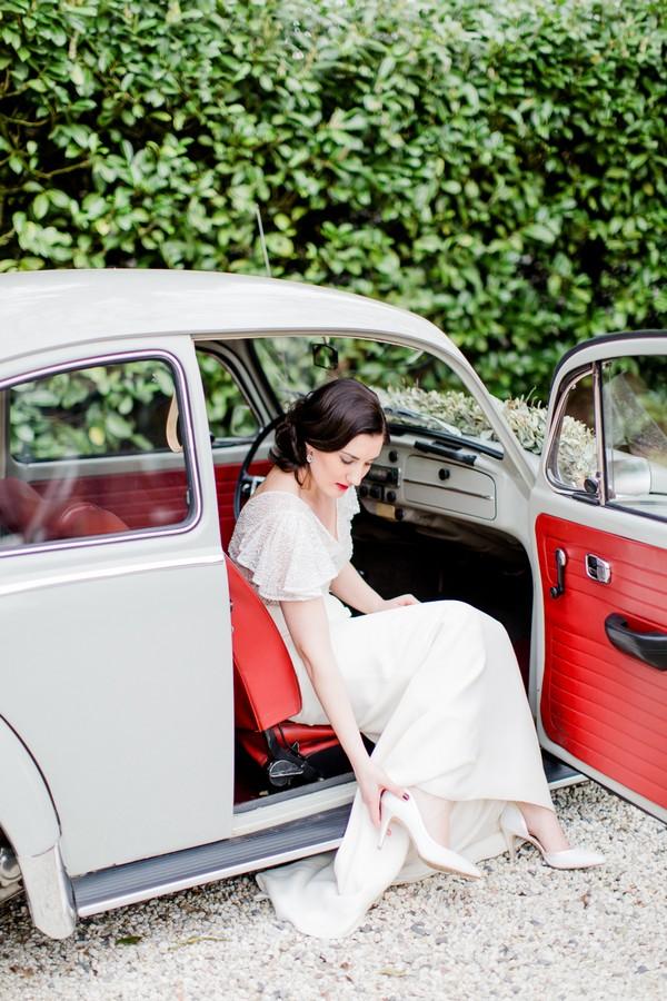 Bride sitting in vintage VW Beetle