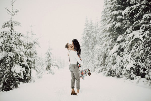 Man lifting fiancée up in snow