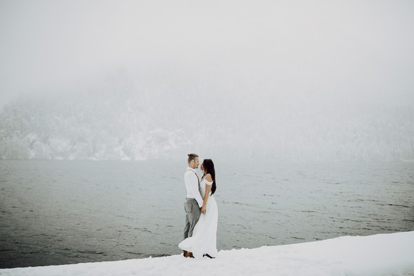 Couple standing in snow next to water