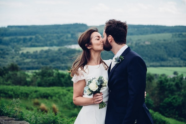 Bride and groom kissing in Scottish countryside