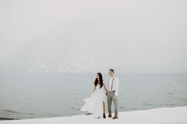 Couple standing next to water in the snow