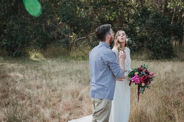 Bride and groom blowing dandelion