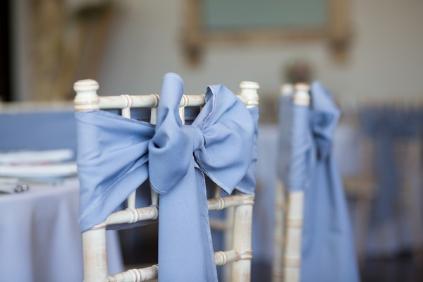 Blue bow tied to back of wedding chair