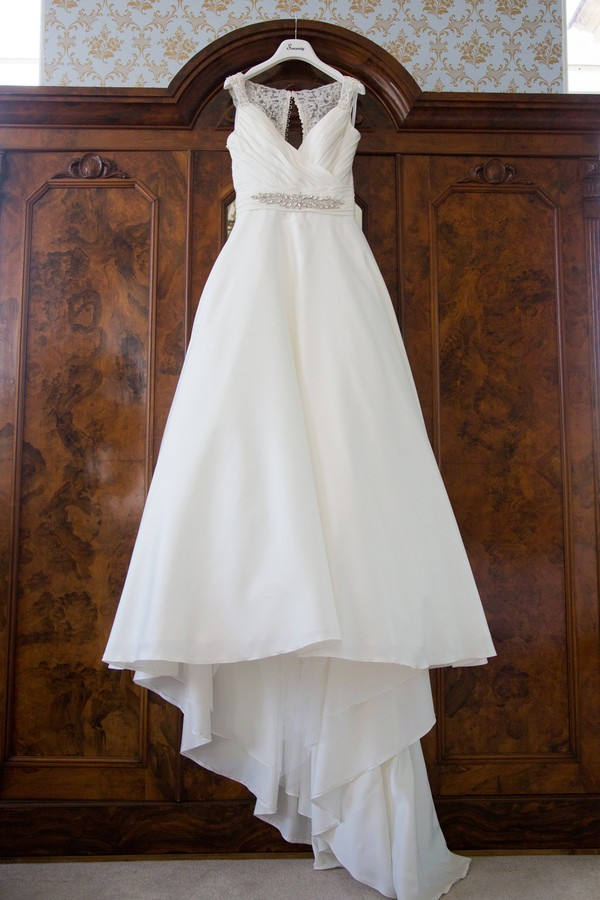 Wedding dress hanging on front of wardrobe