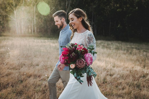 Bride holding bouquet as she walks with groom