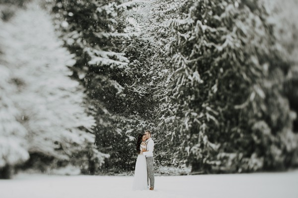 Couple standing in woodland in snow