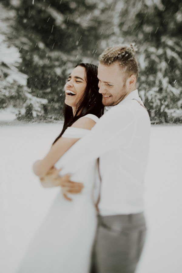 Woman laughing as fiancé holds her from behind