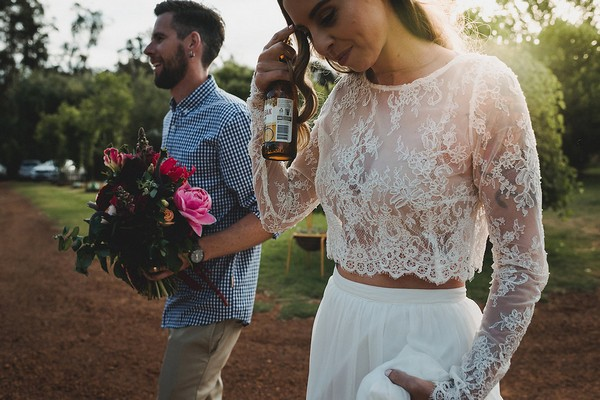 Bride holding bottle of beer and groom holding bouquet